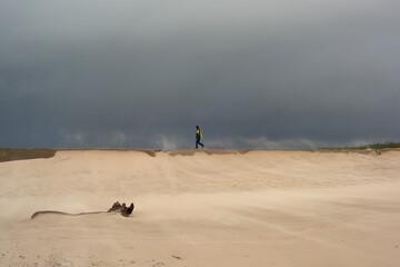Fototapeta Sztorm na morzu bałtyckim, a na plaży piaskowe szaleństwo. Strumień piasku smaga po twarzy, silny wiatr unosi smugi pyłu i utrudnia spacer. Chłopiec spaceruje po falochronie. obraz