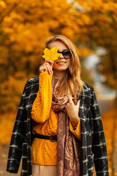 Stylish portrait of a pretty happy girl with a smile with sunglasses in a vintage knitted sweater, black coat and a scarf covers face with an autumn yellow maple leaf in a amazing park with foliage