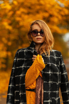 Beautiful European girl with fashionable sunglasses in a stylish black coat and a yellow knitted sweater against the background of a colorful park with autumn foliage