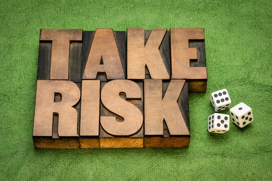 take risk word abstract in vintage letterpress wood type against green textured paper with dices, business, danger and uncertainty concept