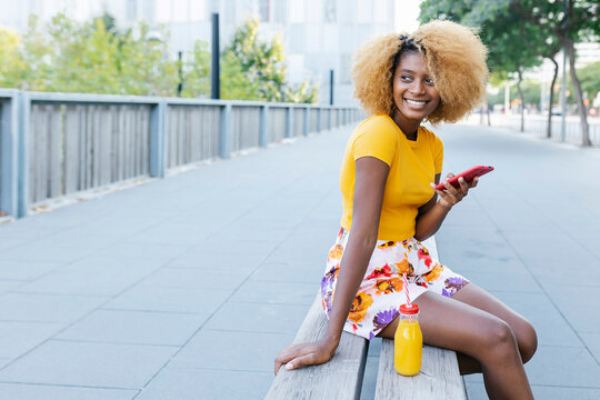 Smiling young african american woman using mobile phone and drinking orange juice while sitting on bench in city street - Copy space for text on the left
