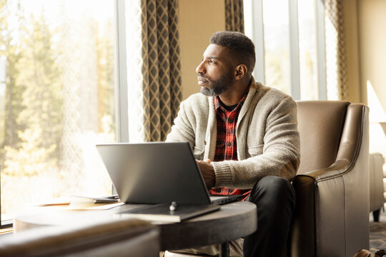 Man working on laptop in hotel lobby