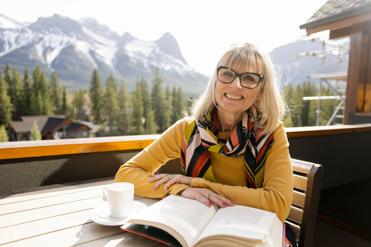Portrait of woman with book on balcony with mountain view