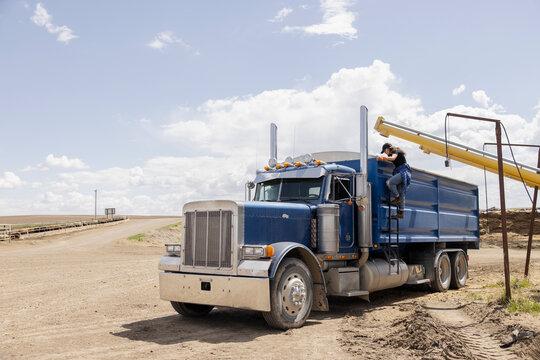 Female farmer on ladder of tractor trailer semi truck on farm