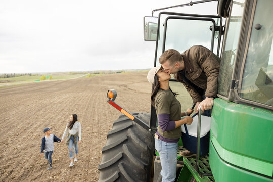 Affectionate farmer couple kissing at tractor on rural farm
