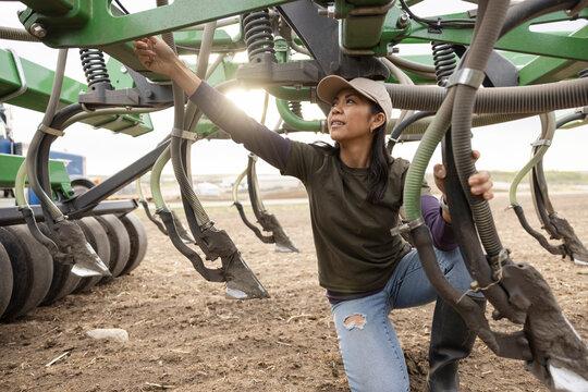 Female farmer inspecting combine harvester on rural farm