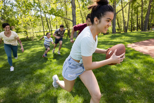 Cheerful daughter running with football at game in park