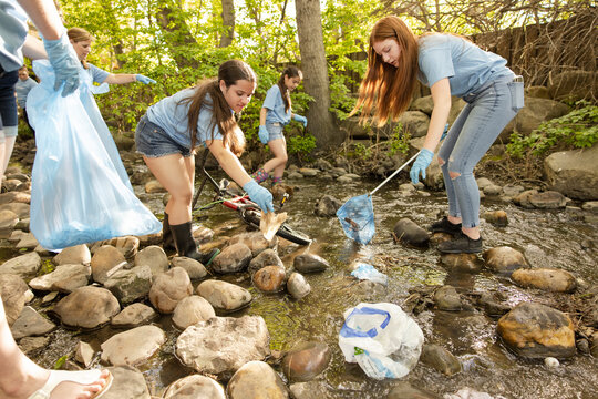 Group of young volunteers cleaning up rubbish from river