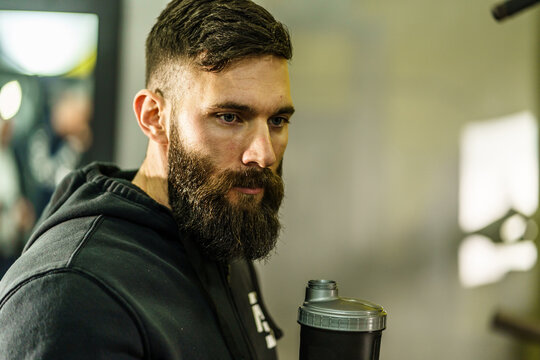 Front view portrait of young caucasian man athlete in black hoodie male standing in the gym holding protein supplement shaker supplementation in training waist up black hair and beard copy space
