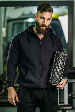 Front view portrait of male athlete standing at gym holding foam massage roller