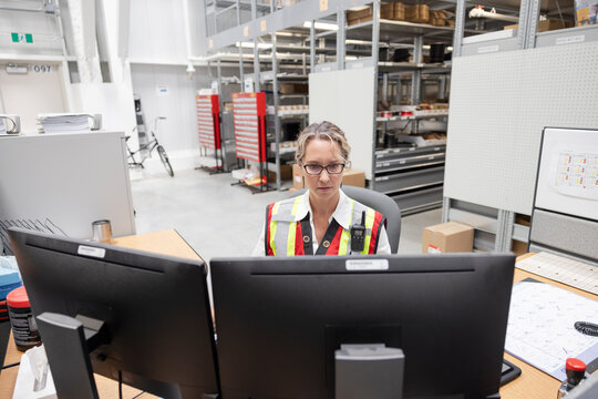 Female supervisor working at computers in parts warehouse office