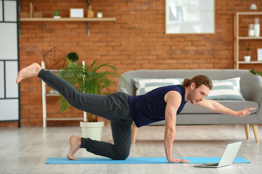 Young man practicing yoga at home
