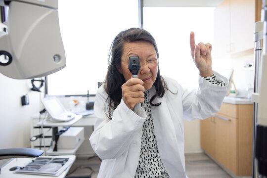 POV female optometrist using ophthalmoscope in eye exam