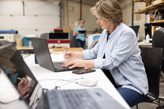 Senior female maker working at laptop in workshop