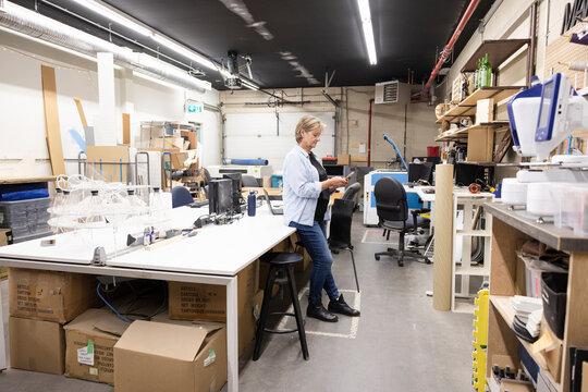 Senior female maker using smart phone in workshop