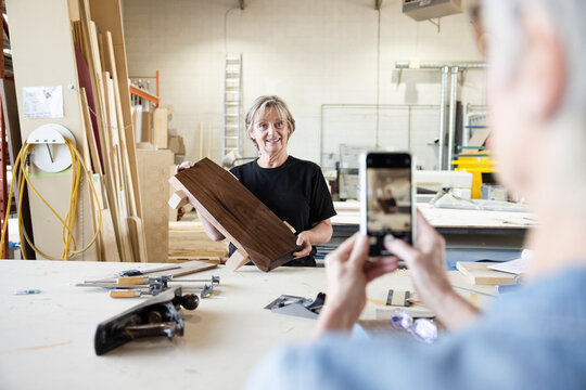 Senior female woodworker posing for photo with wood in workshop