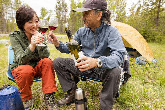 Couple drinking wine next to campfire