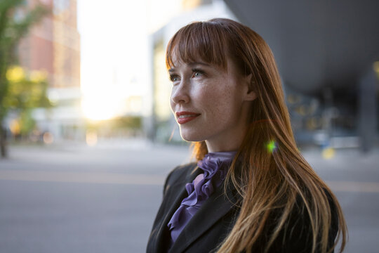 Portrait ambitious businesswoman on city street