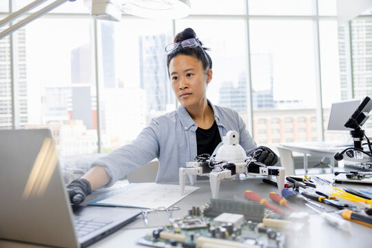 Female robotics engineer working at laptop in office