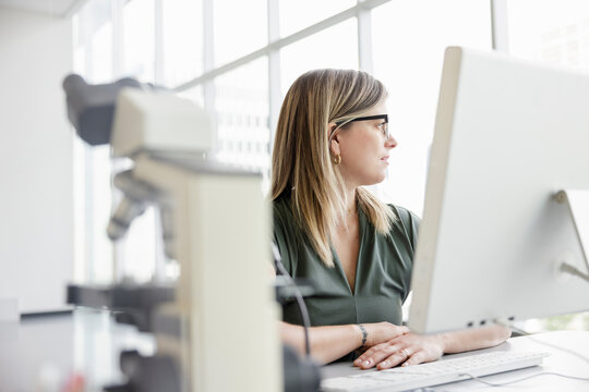 Thoughtful female scientist at computer looking away
