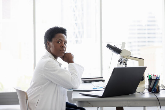 Portrait confident female scientist working at laptop in laboratory
