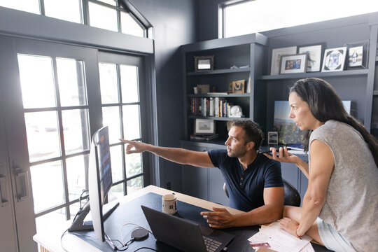 Couple working at computer in home office