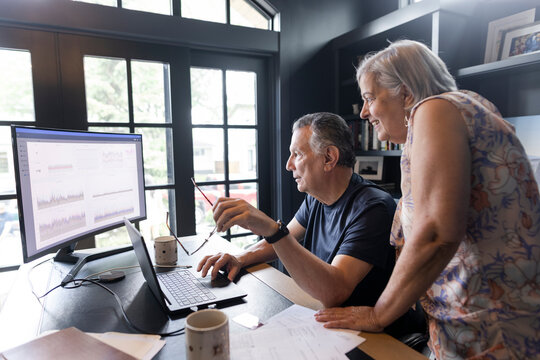 Senior couple working at laptop in home office