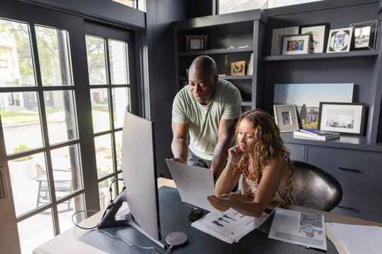 Couple with paperwork working at desk in home office
