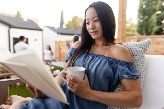 Woman relaxing with coffee and reading book on patio