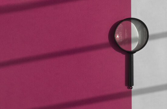 Black magnifier over bright purple background. Search tool on banner with copy space.