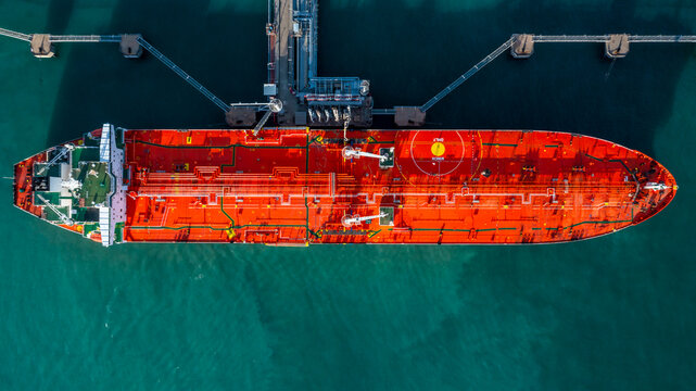 Aerial view tanker ship vessel unloading at port, Business import export oil and gas petrochemical with tanker ship transportation oil from dock refinery, Loading arm oil and gas offshore platforms.