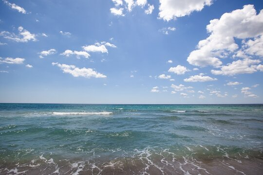 A summer vacation background of a tropical beach and blue sea and white clouds