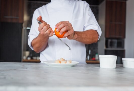 Chef hand cooking penne with cheeze and sun-dried in a white plate