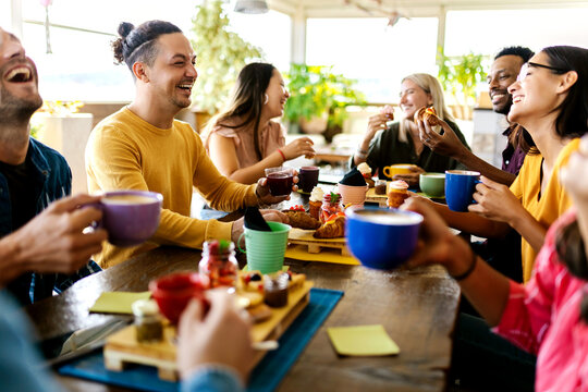 Smiling group of diverse friends having breakfast and talking at coffee bar restaurant - Happy millennial multiracial people laughing and having fun together while drinking cappuccino indoors -