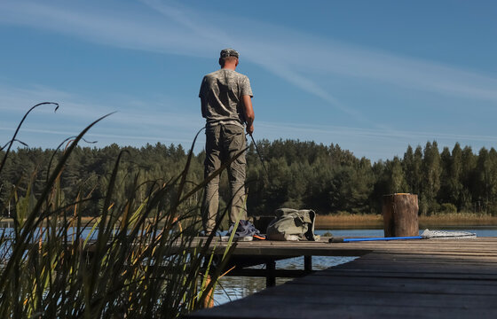 Fisherman on wooden pier catching fishes on reel rod, standing in summer near lake.