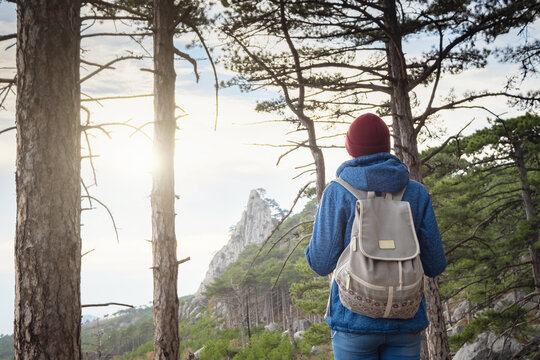 the concept of discovery and hiking, nature and freedom. woman is hiking in mountain, with a backpack climbs to the top of the mountain against the background of sunset . Active retirement.