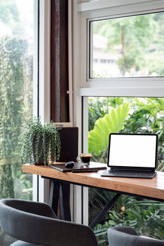 Blank screen tablet with magic keyboard and coffee cup on wooden table in cafe room, vertical view.