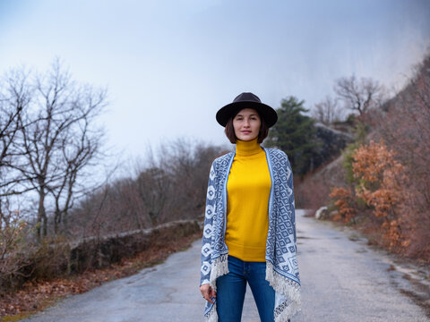 Stylish hipster woman in hat and poncho walking down a mountain road. The concept of travel and wanderlust. An amazing atmospheric moment