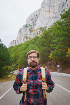 Male hipster Traveler with backpack in plaid shirt and jeans hiking in the mountains travel, trekking in autumn countryside, road in the mountains