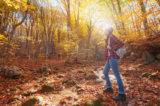 Woman hiking looking at scenic view of autumn foliage mountain landscape. Outdoor adventure travel lady standing relaxing and hiking in nature in autumn season.