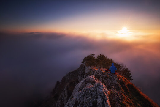 Dramatic Silhouette Of Man Sitting On Mountain Ridge Over Looking misty Skies