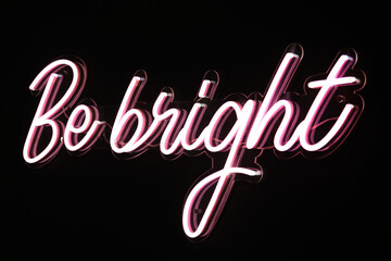 Be bright phrase in pink flashing neon letters over black background.