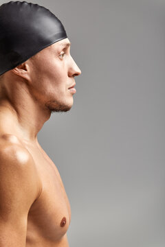portrait of a young man swimmer wearing a rubber hat, standing against a gray background hat getting ready for training, profile view
