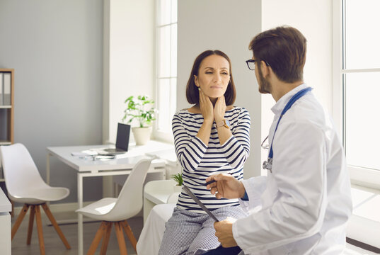 Lady with inflamed tonsil glands visits doctor at clinic. Worried woman asks specialist to help reduce neck pain. Man who works as general practitioner talking to female patient with sore lymph nodes
