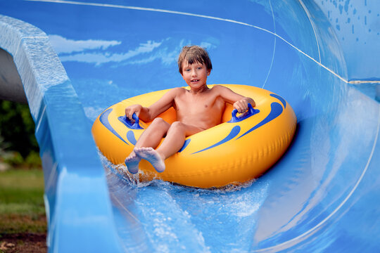 happy an 8 year old boy is riding in the water Park on inflatable circles on water slides with splash