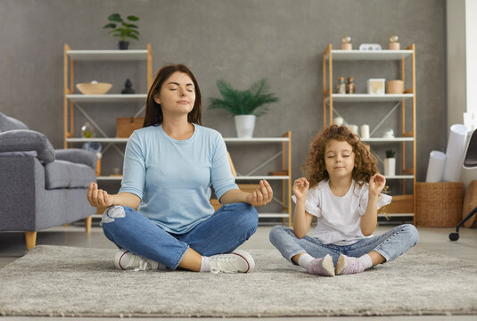 Calm young Caucasian mom and 7s daughter sit on floor with mudra hands meditate relieve negative emotions. Relaxed mother and small teen girl child rest practice yoga together. Stress free concept.
