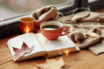 season, leisure and objects concept - cup of coffee, book, autumn leaves and candle on window sill...