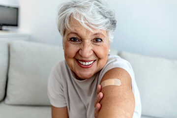 Obraz Cropped shot of a smile senior woman 70s after receiving the coronavirus covid-19 vaccine. Old aged woman posing with an adhesive COVID-19 and adhesive bandage on her upper arm. Vaccination concept. - fototapety do salonu