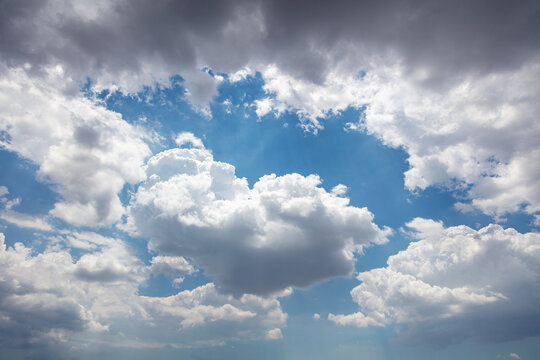 Fluffy cumulus clouds on blue sky background. Cloudscape white and grey color