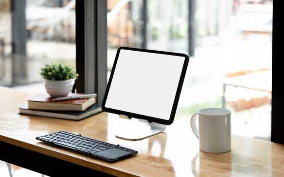 Portable workspace with blank screen tablet on wooden desk with copy space and decorations in coffee shop.